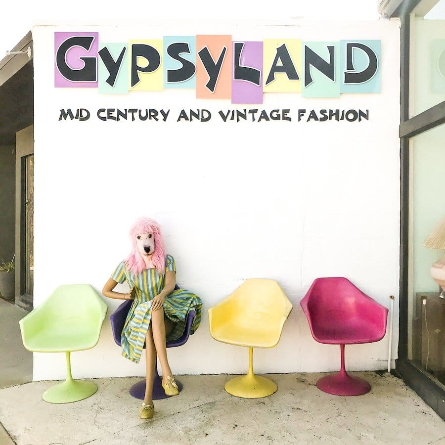 Exterior of Gypsyland in Palm Springs including 4 vintage, colorful chairs, 1 mannequin wearing a pink poodle mask is sitting in a chair