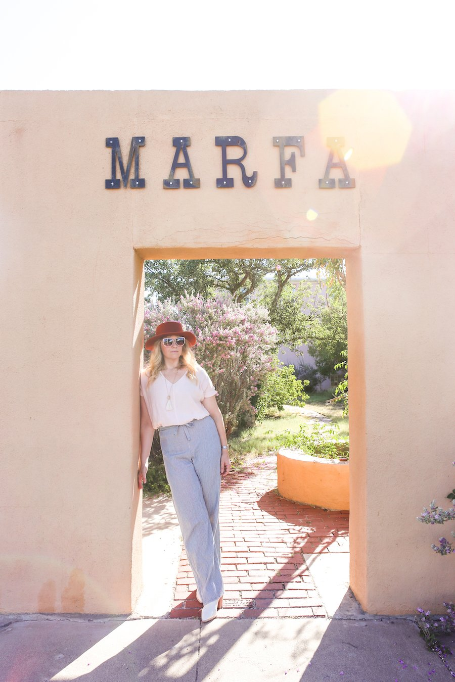 Woman leaning against wall under the word Marfa in Marfa, Texas