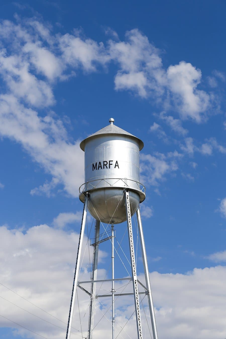 Water tower with word Marfa on it against blue sky with clouds in Marfa, Texas