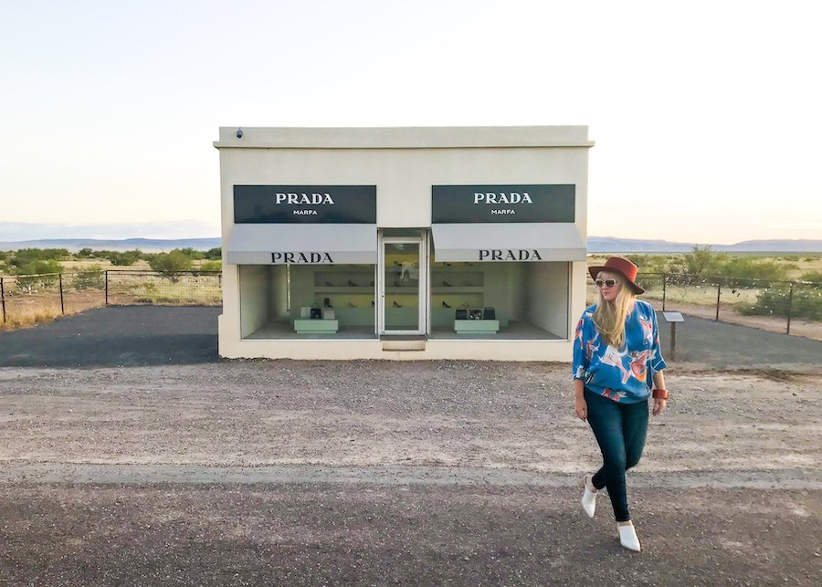 Woman walking in front of Prada Marfa art installation outside of Marfa, Texas