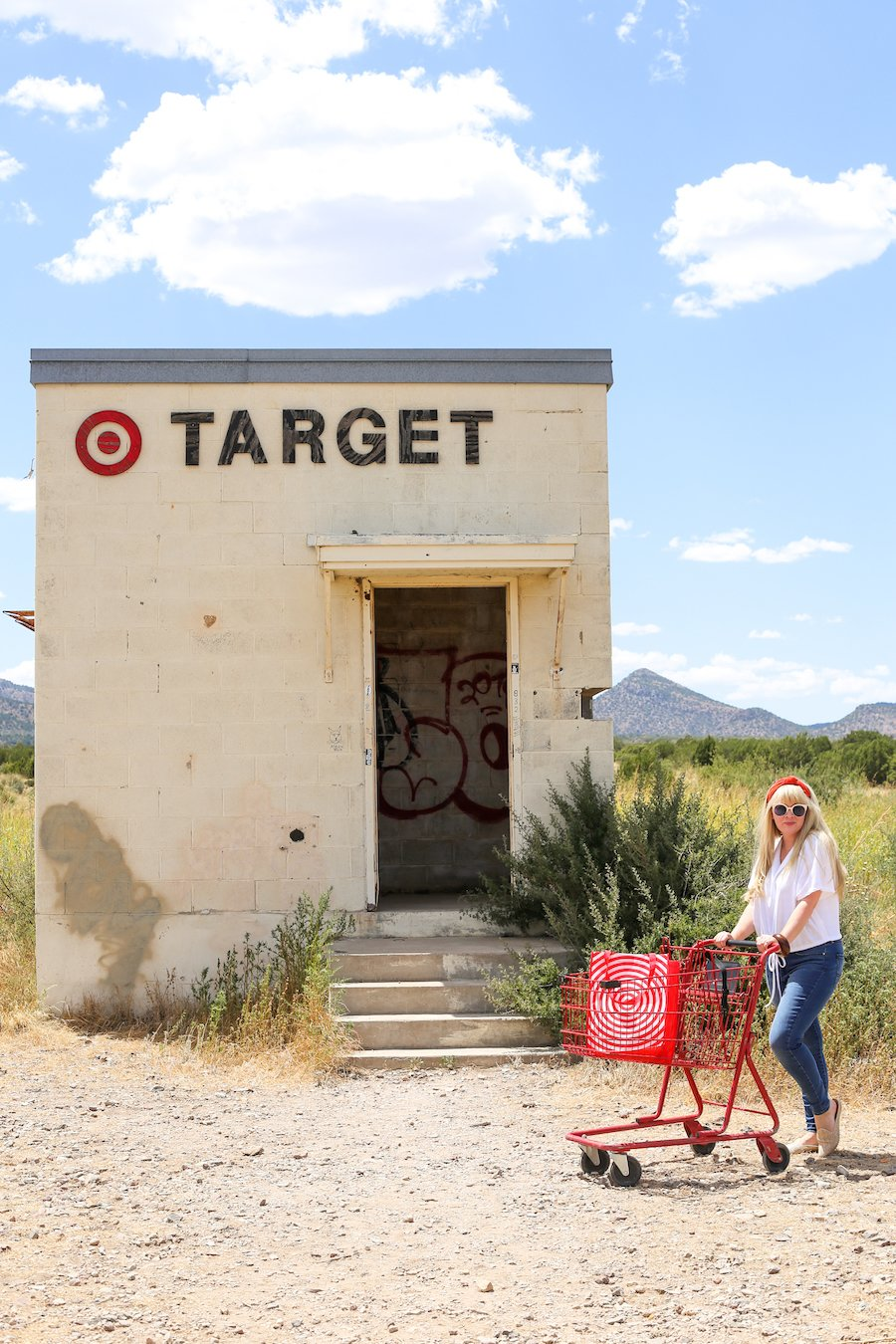 Woman pushing red shopping cart in front of fake Tiny Target near Marfa, Texas
