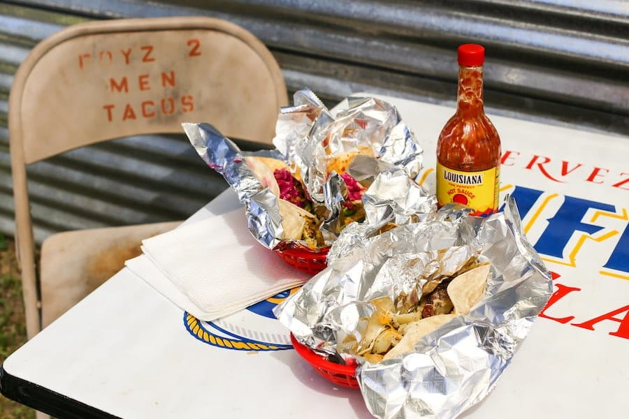 Boyz II Men breakfast tacos wrapped in foil with hot sauce on a table in Marfa, Texas