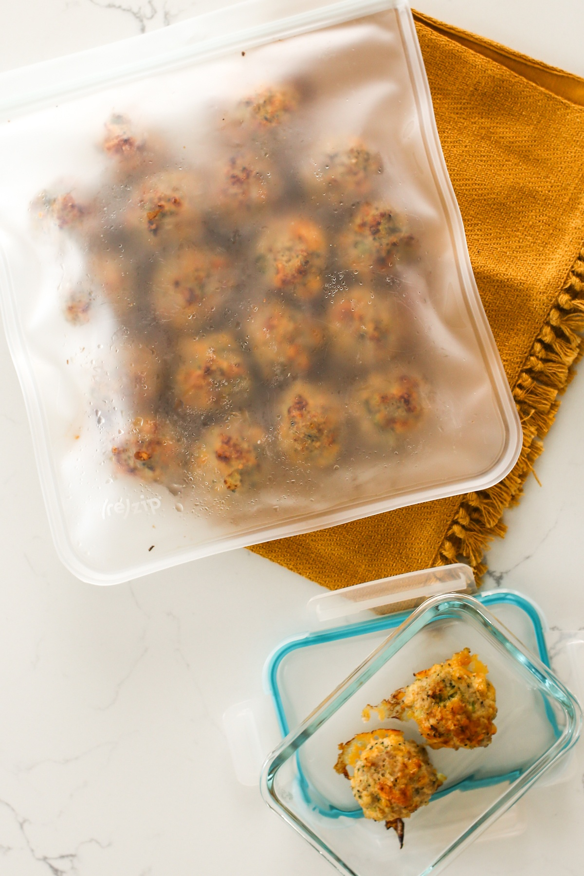 Cheesy Broccoli Turkey Meatballs in a freezer bag with 2 additional meatballs in a glass food storage container