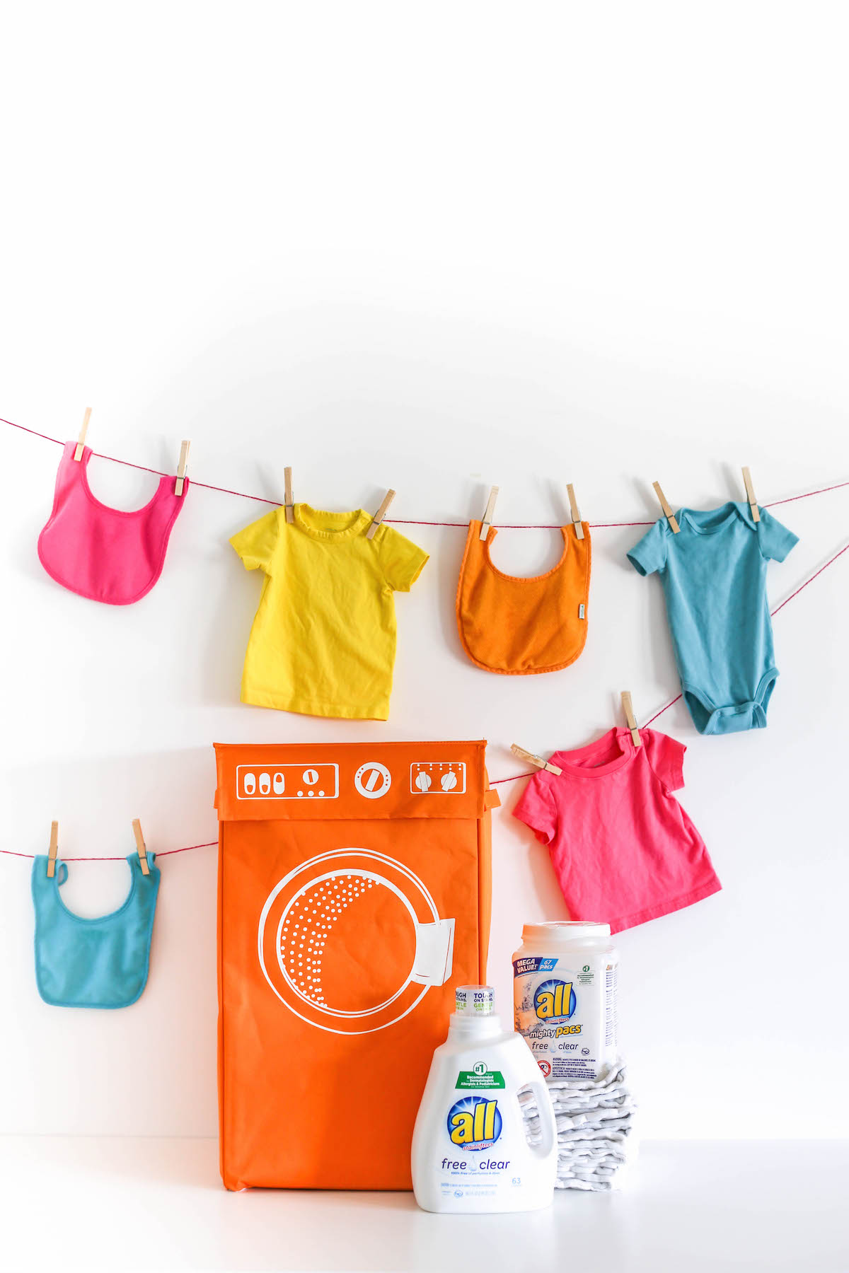 Baby clothes hanging on rope with a hamper and laundry detergent